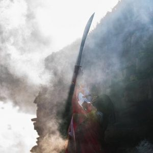 Smoky outline of woman holding a long fighting sword up into the air