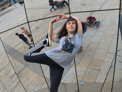 Girl with brown hair standing on one foot in a yoga pose holding her foot on top of a cement bollard in front of a large circular mirrored sculpture