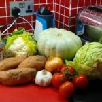 a red tiled corner kitchen surface with sweet potatoes an acorn squash and various fresh vegetables