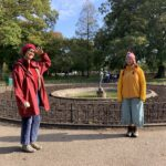 The two artists, Anushiye and Jo standing in front of a circular empty flower border in Thompson's Park Cardiff
